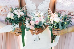 Bride and bridesmaid are holding bouquets of flowers in hands. Wedding d etails.