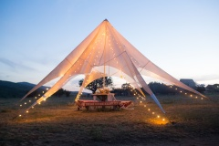 Boho wedding tent in the open air for the bride and groom with decorations, flowers, lights.